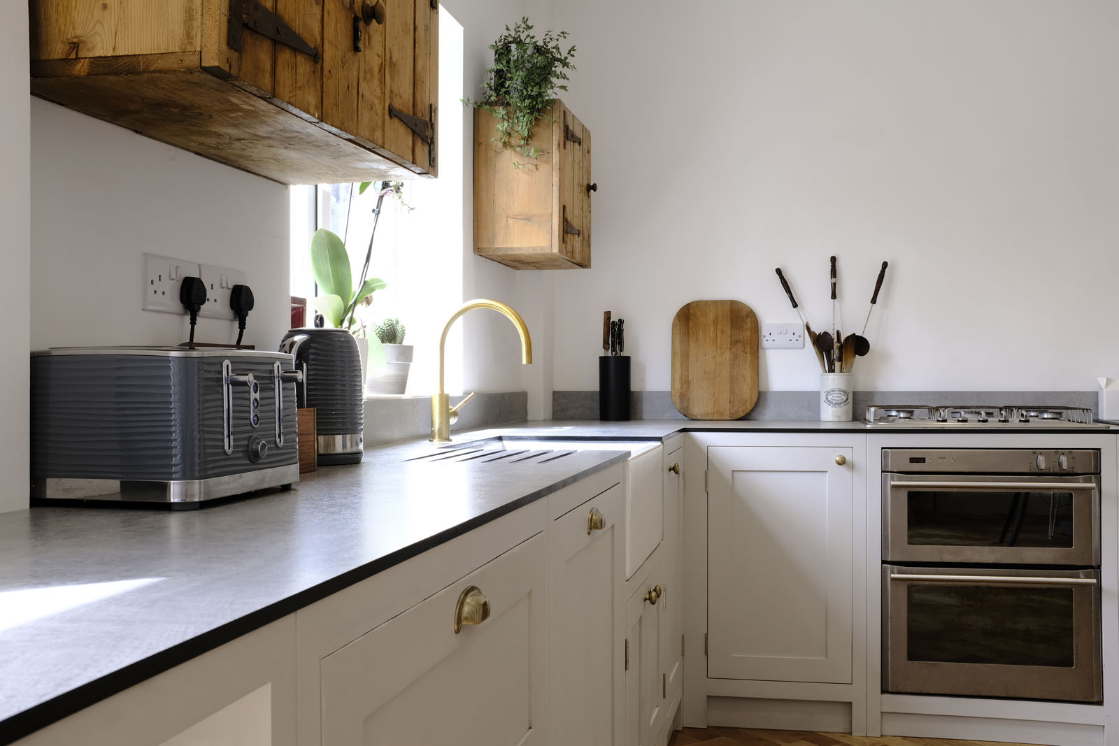 White shaker kitchen with gold details and wooden cupboards