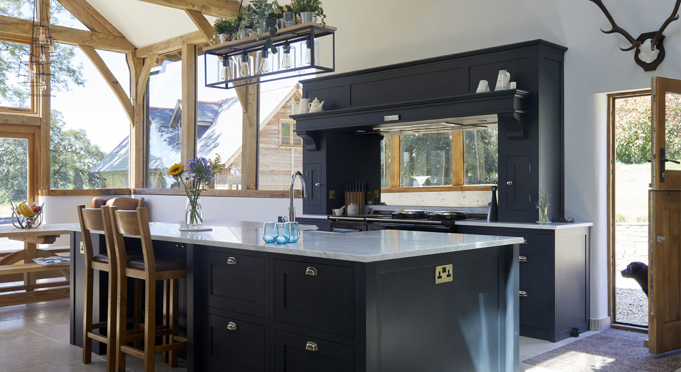 Dark Grey Black shaker Kitchen Design with large island, wooden beams and dog in doorway.