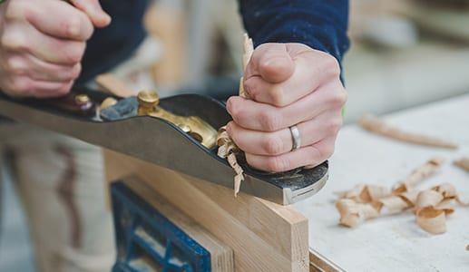 Hands using a tool to carve the wood for a handcrafted shaker kitchen