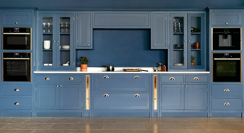 All blue shaker kitchen with white worktops and gold handles.