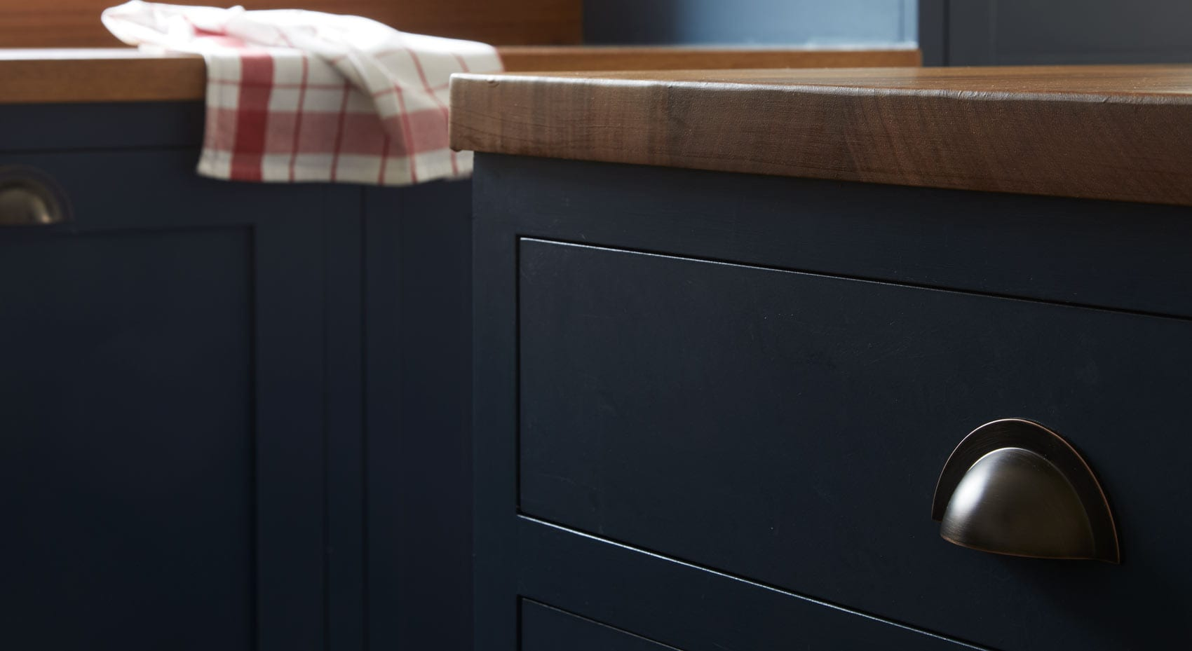 Close up of dark grey shaker kitchen cabinets with wooden counters.