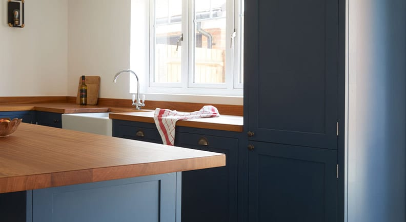 Close up of dark grey shaker kitchen with wooden counters.