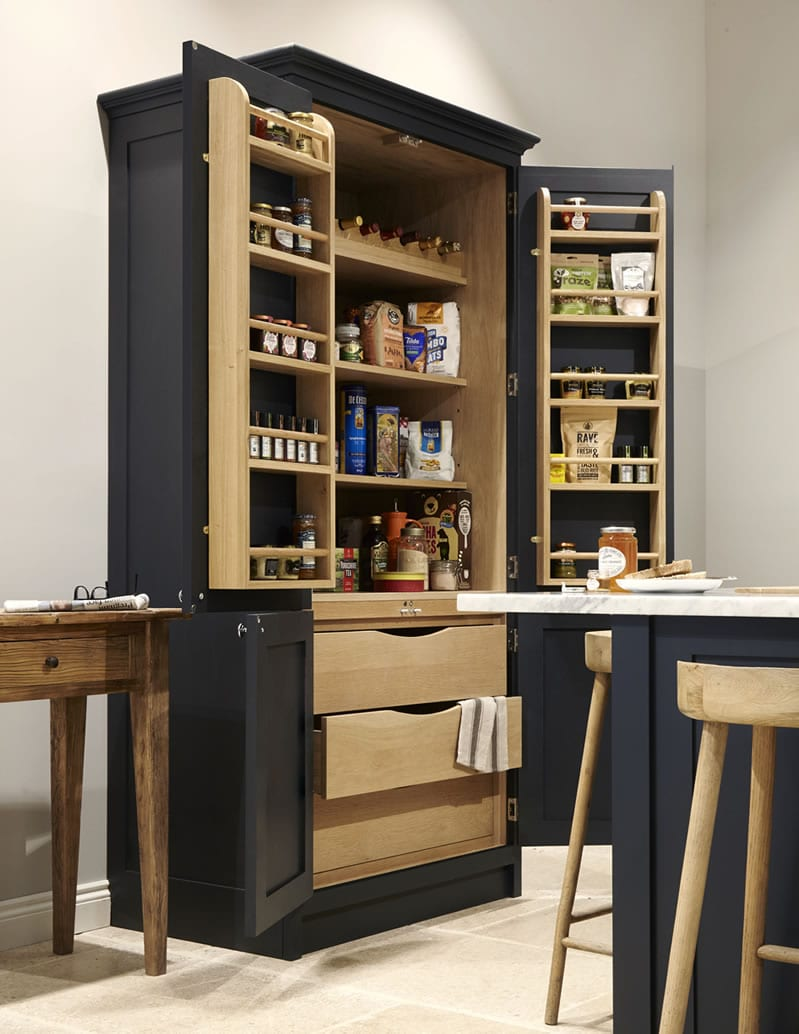 Navy shaker kitchen with bespoke cabinetry and open cupboards with food in.
