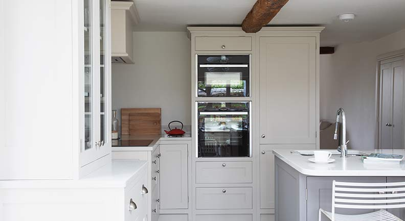Light grey and Ivory shaker kitchen design with high cupboards and island feature.