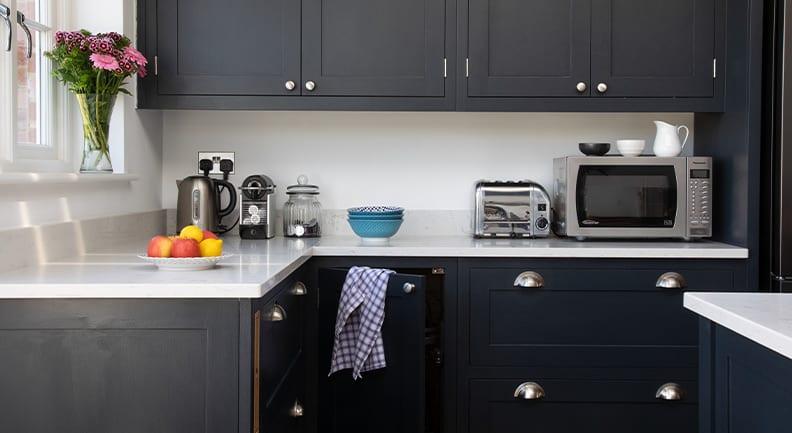 Close up of dark grey shaker kitchen design with white stone worktops