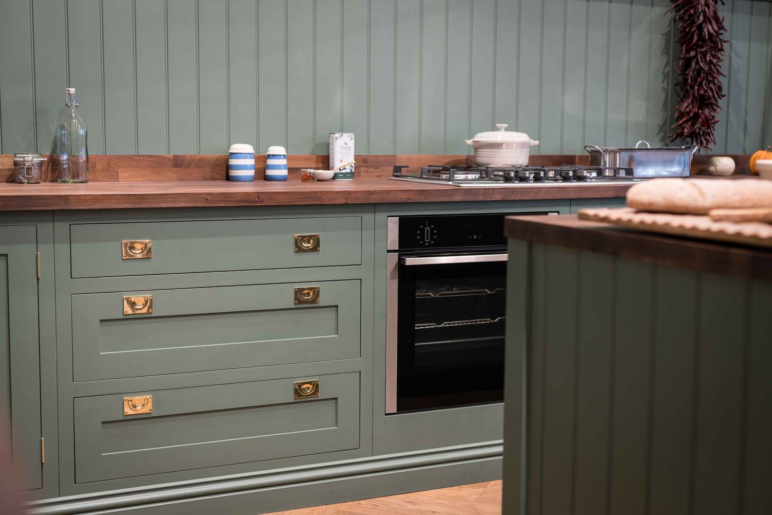 Green shaker kitchen with wooden worktop and gold handles