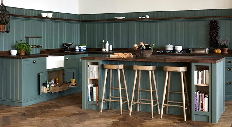 Rustic Green shaker kitchen with dark wood worktop and wooden stools a an Island