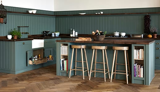 Green shaker kitchen with three wooden stools at an island