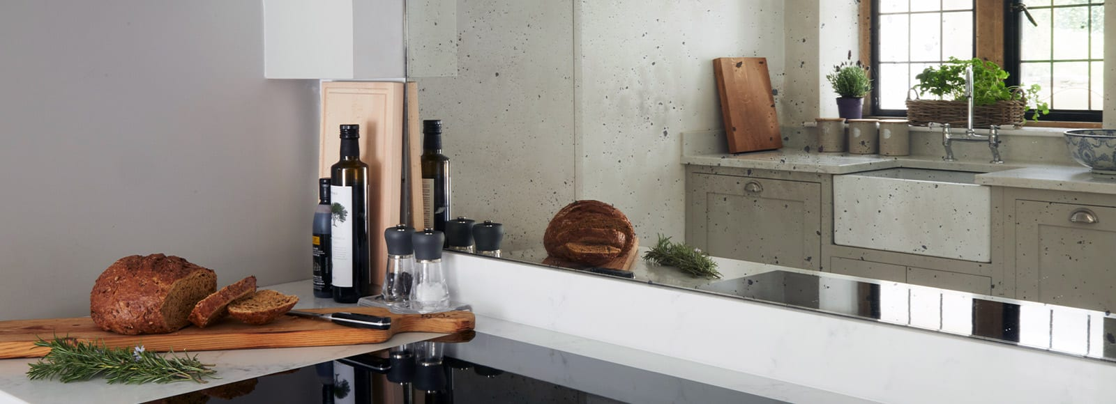 Green shaker kitchen reflection in a mirrored splashback with bread on side.