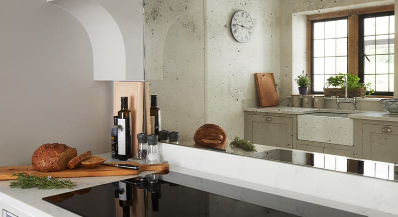 Shaker kitchen reflection in mirrored splash back with stone worktop.