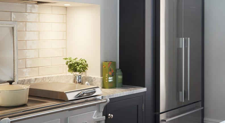 Dark grey shaker kitchen with large silver fridge and marble stone worktop.