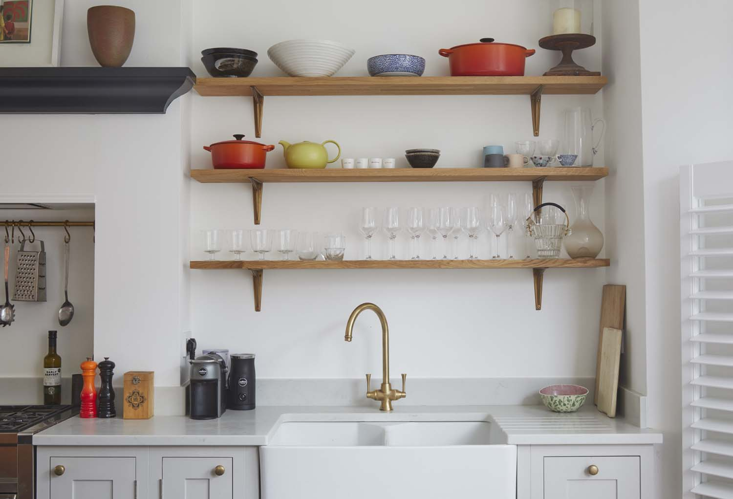 Light grey shaker kitchen with wooden shelving and large sink.
