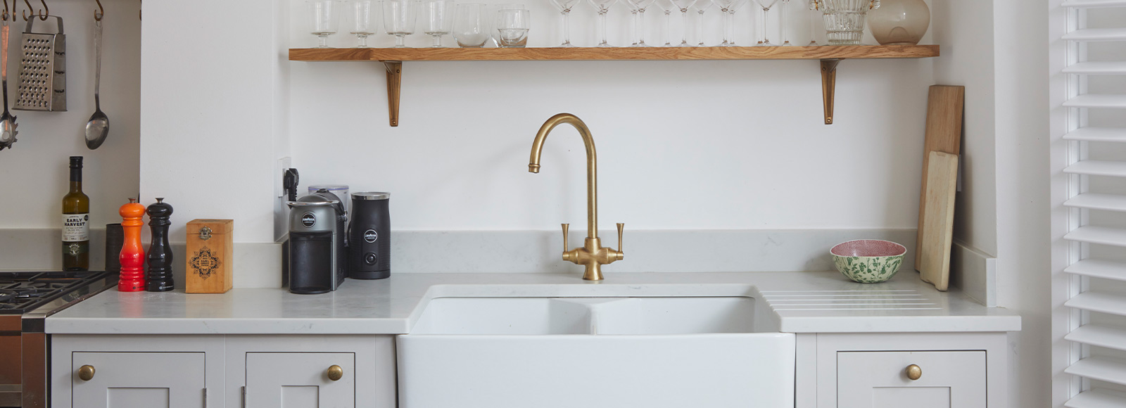 Light grey kitchen with large sink, gold tap and wooden shelf