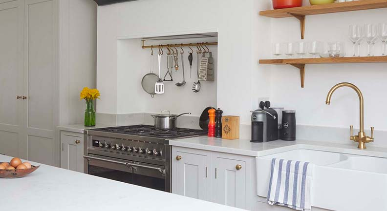 Neutral shaker kitchen design with large oven, wooden shelves and white stone worktops