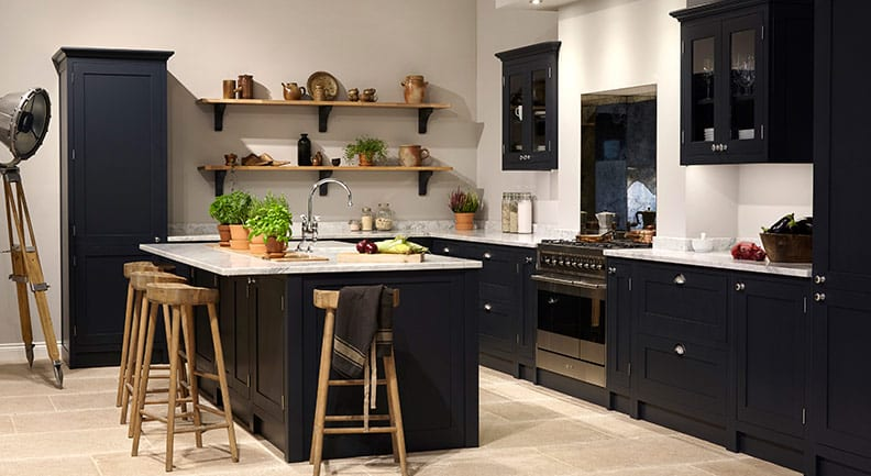 Navy shaker kitchen with wooden shelves and stools and white stone worktop