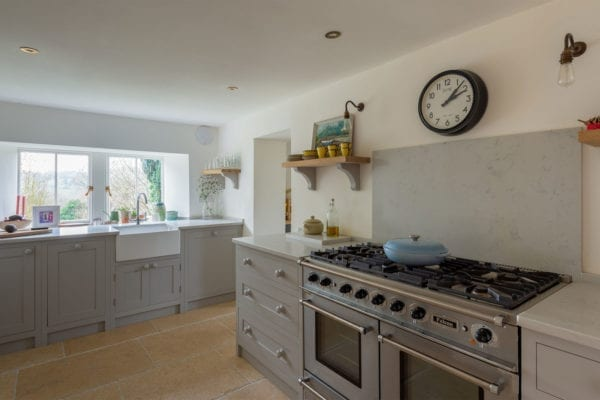 A Light grey shaker kitchen design with white walls and large oven