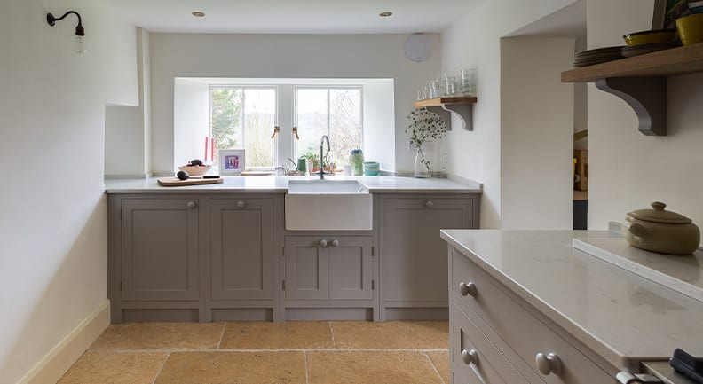 Light grey shaker kitchen with white stone worktops by Olive & Barr
